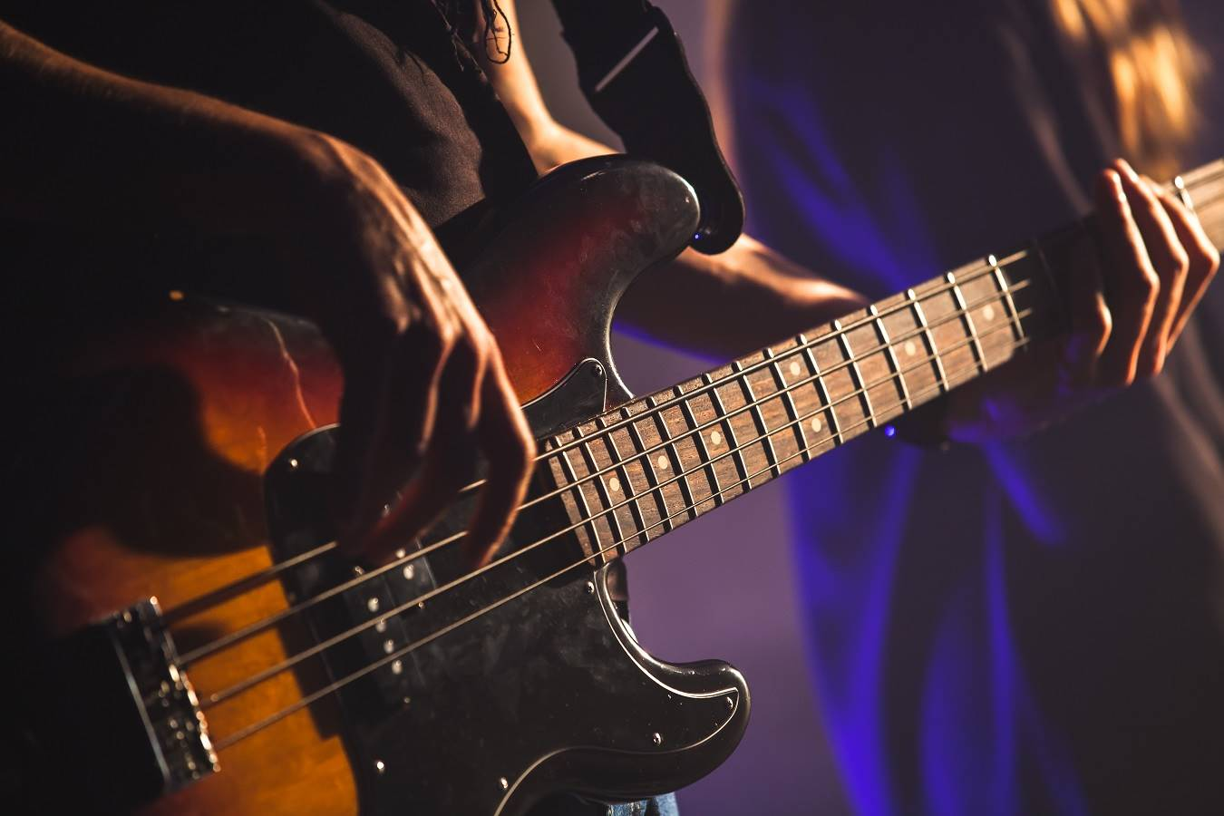 Closeup photo of bass guitar player hands, soft selective focus, live music theme