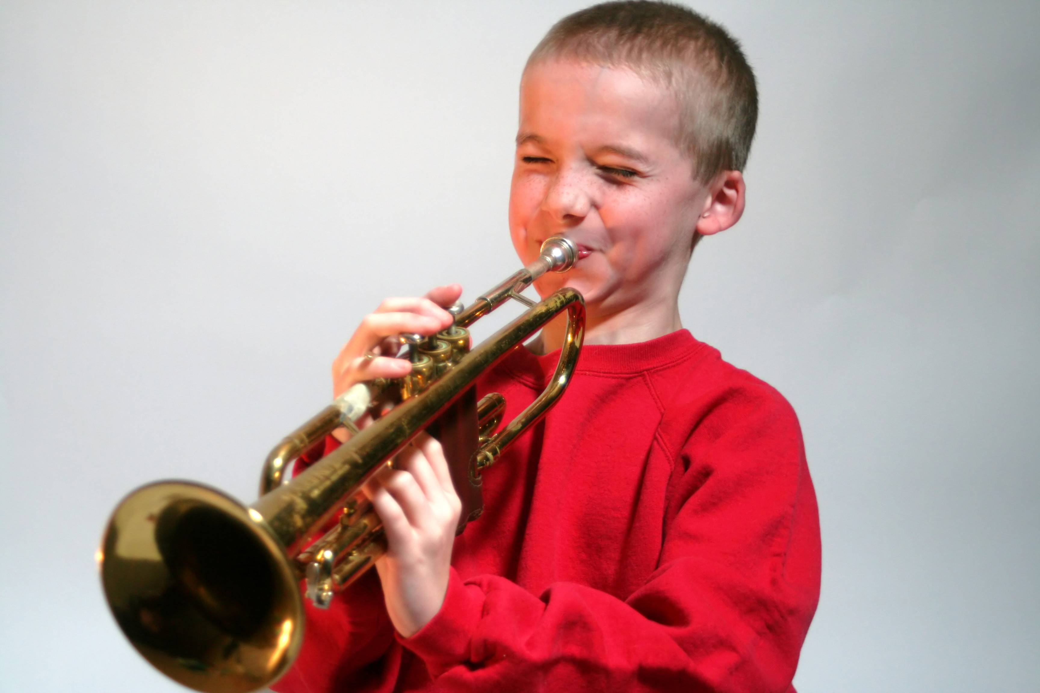Young boy making a face as he attempts to hit a high note on a trumpet, isolated on a light background.