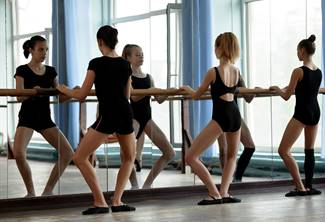 Three ballet dancers warming up before practice starts